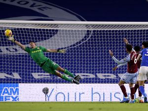 Aston Villa goalkeeper Emiliano Martinez makes a save during the Premier League match at the AMEX Stadium, Brighton. Picture date: Saturday February 13, 2021..