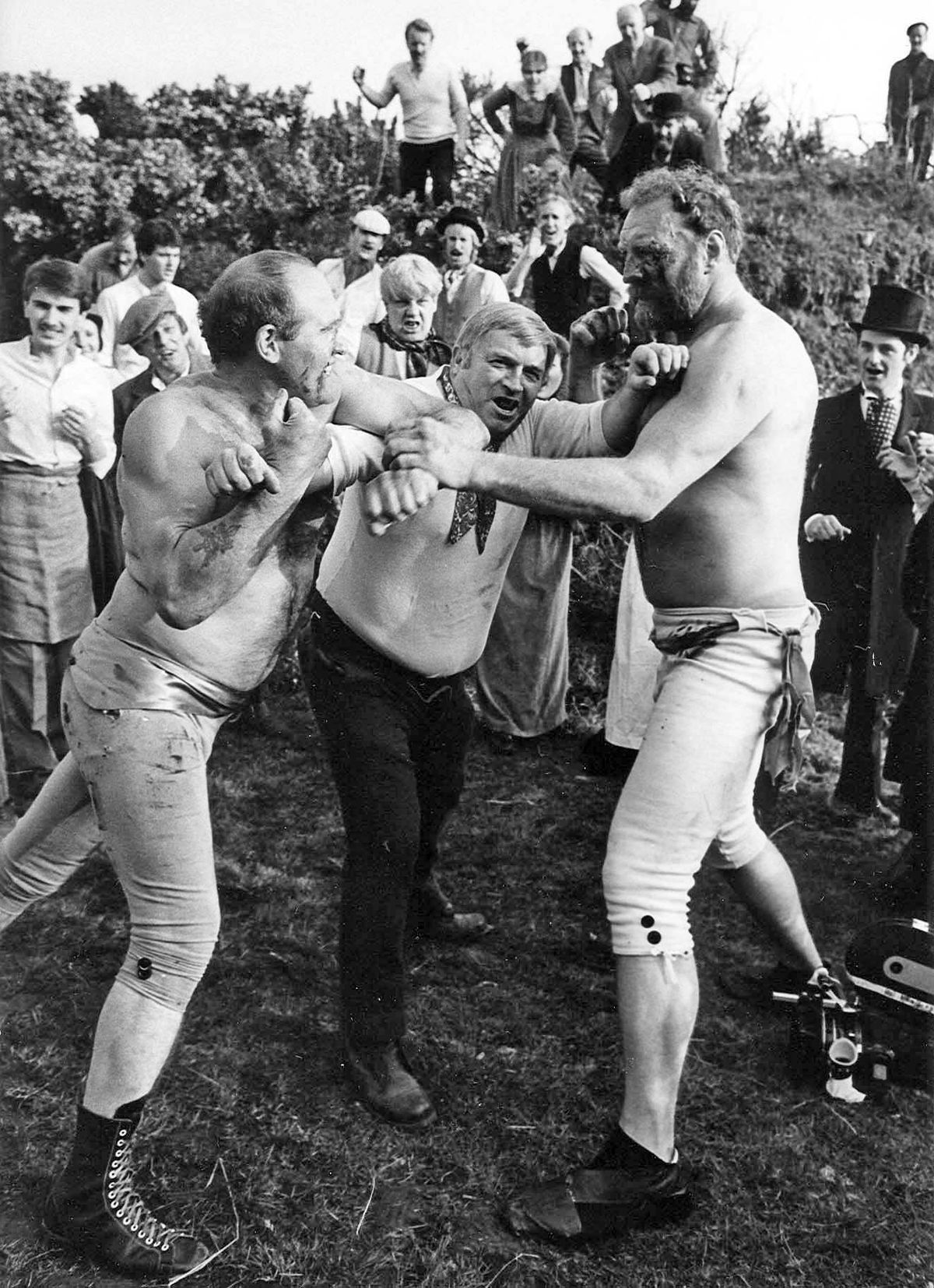 Actors Gordon Corbet (left) and Pat Roach (right) are refereed by Ray Hingley during filming of the bloody bare Knuckle fight between the Tipton  Slasher and his rival Tom Sayers for a TV film shot in Netherton in 1984.