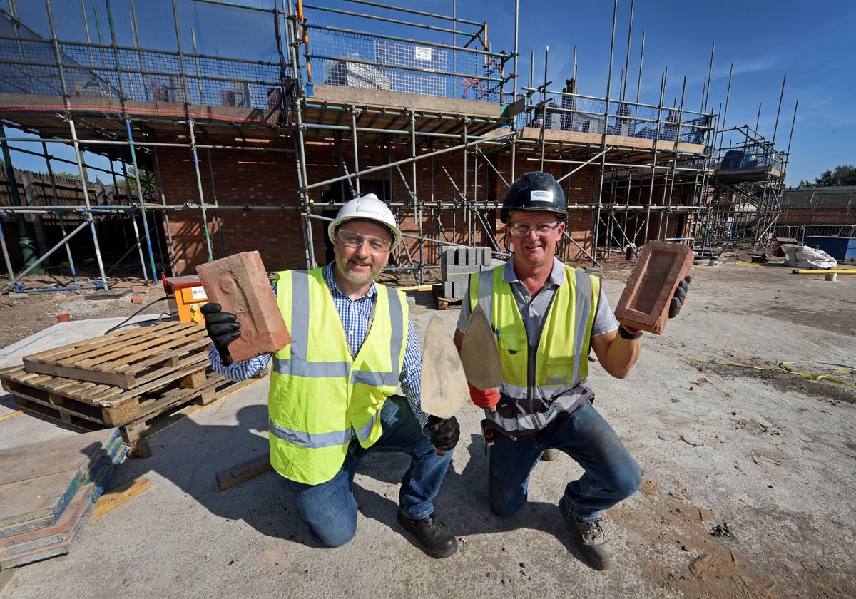 Site supervisor Tim Darrall and project lead John Hughes next to the site, where Tim laid the first brick