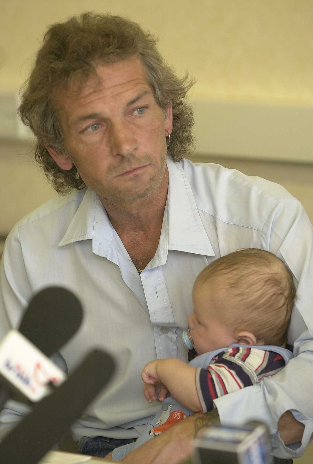 Natalie's father David Putt, holding her son, Rhys McCallum  at a press conference in 2003