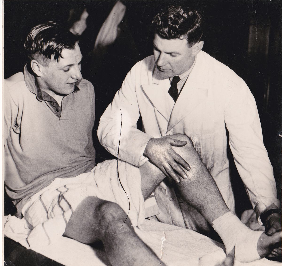 Jack Davies in his other role as club physiotherapist treating Jimmy Mullen