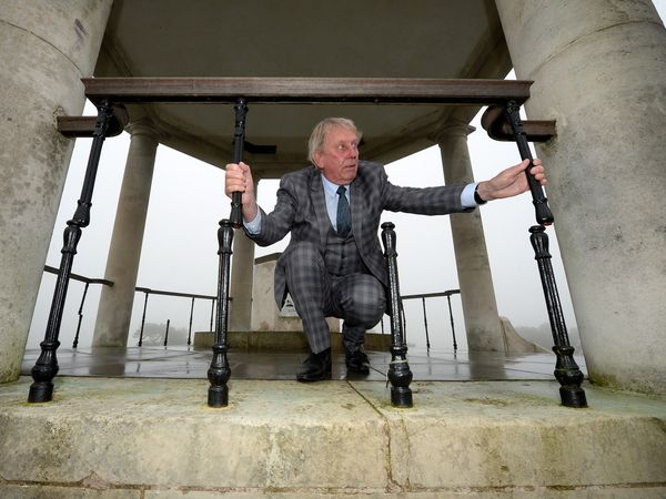 Councillor Chris Towe next to some of the fourteen railings that have been destroyed by vandals at Barr Beacon war memorial