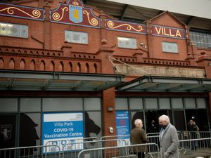 People arrive at a new seven-day vaccination hub at Villa Park, in Birmingham, the home of Premier League club Aston Villa