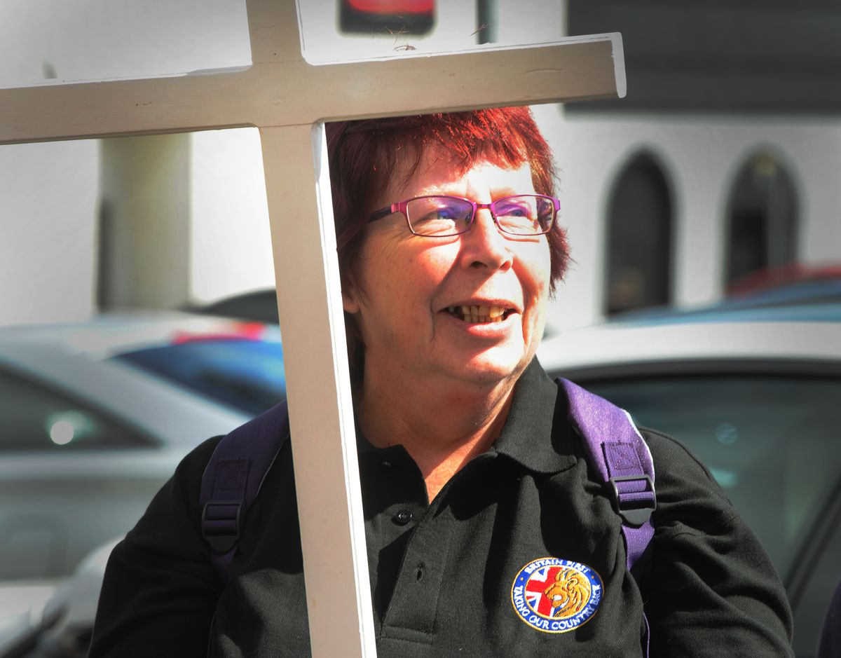 A Britain First activist with a cross in Wolverhampton on Saturday