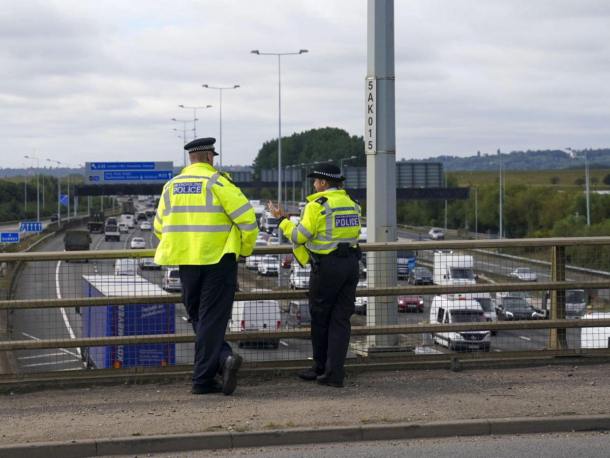 Police officers watch the M25 motorway