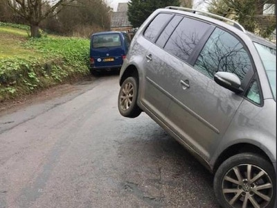 Driver leaves vehicle parked in midair on hilly rural lane