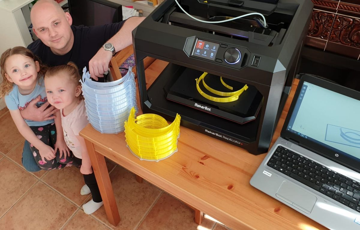 Dudley College tutor Dan Rudge with the college's 3D printer at his home. Pictured with his daughters Amelia, 4, and Georgia, 2