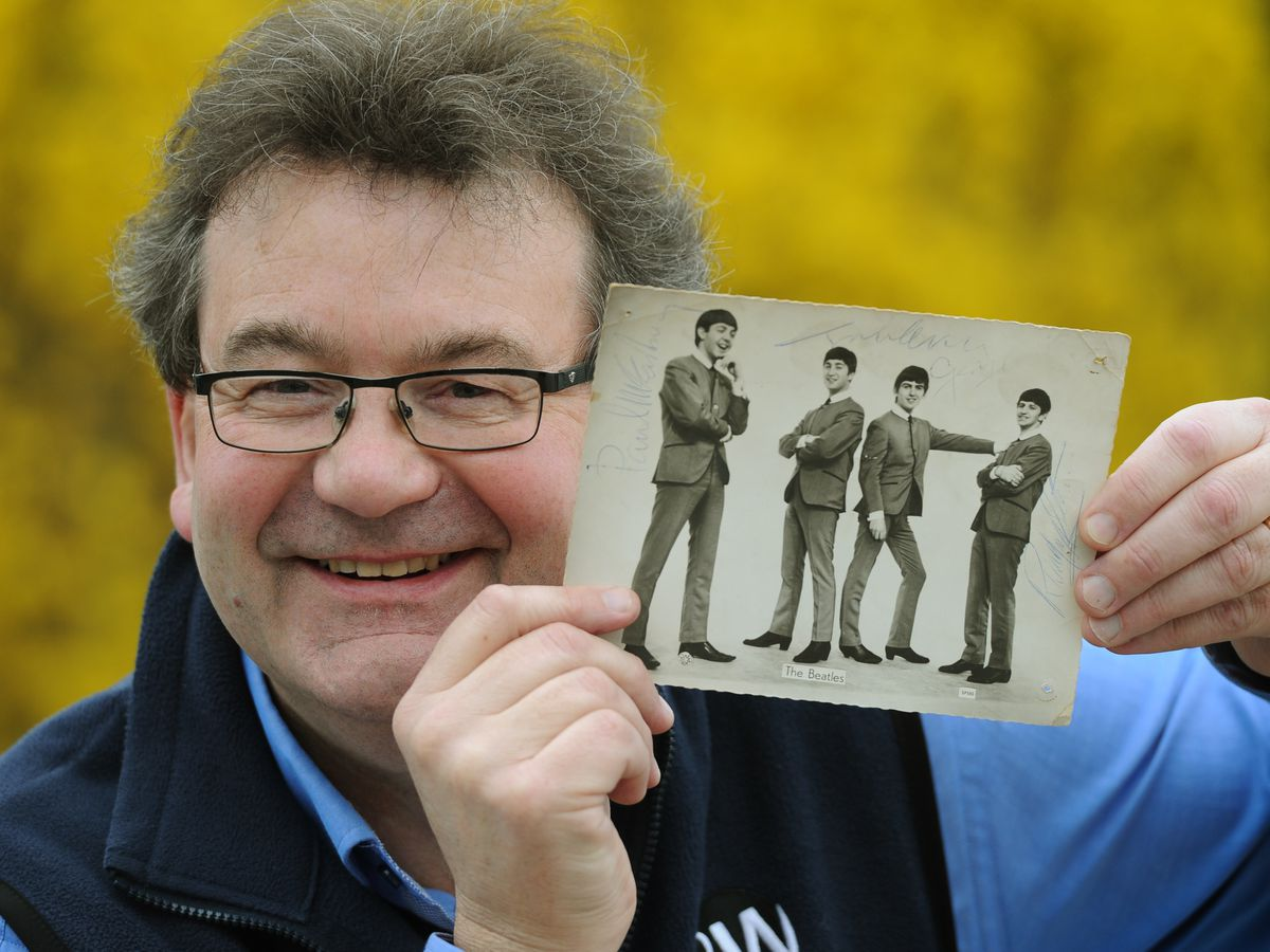 Auctioneer Richard Winterton with the signed photograph of The Beatles