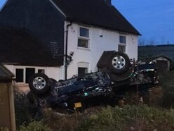 Driver flees after car hits garden wall and overturns