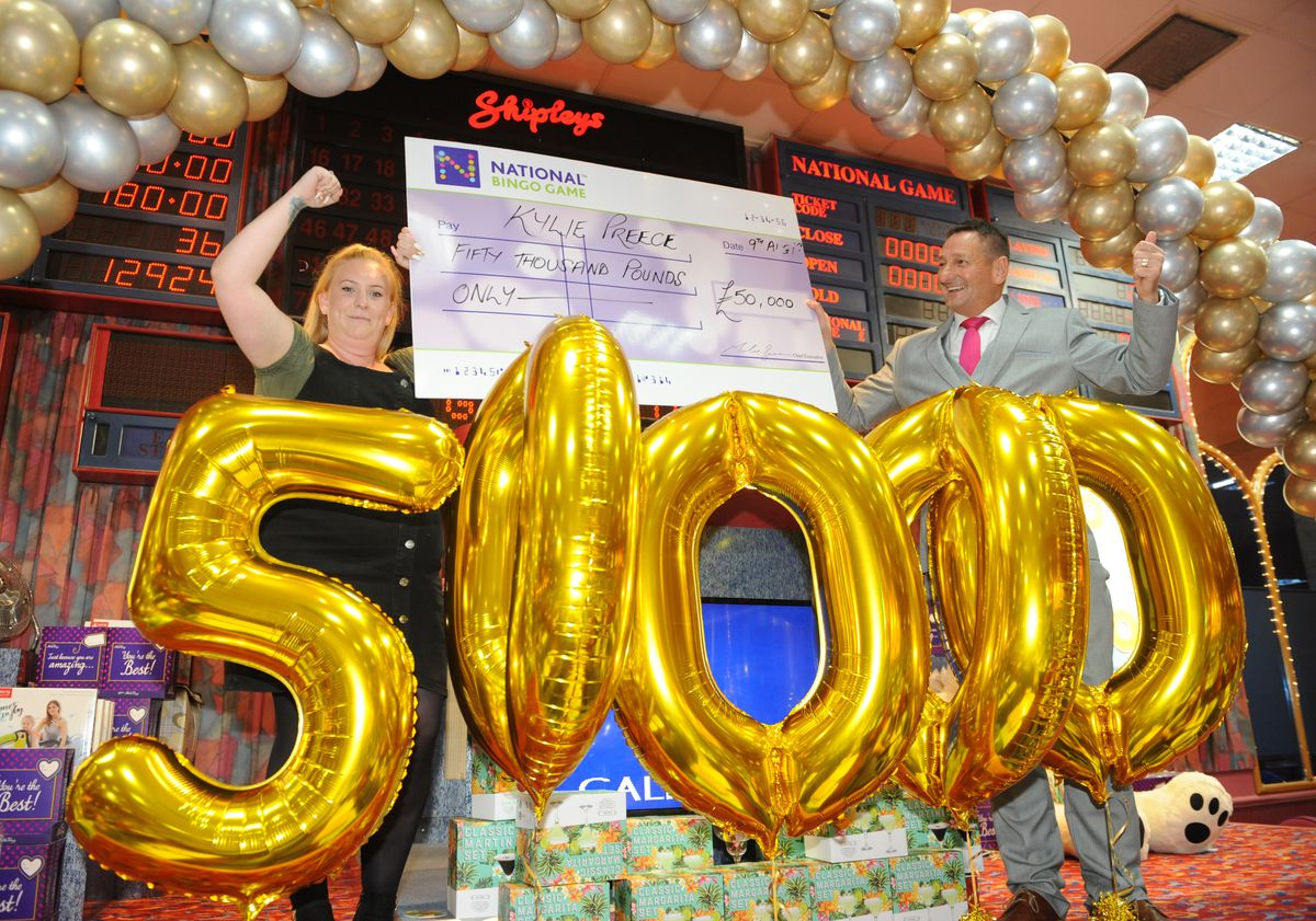 Kylie Preece celebrates winning £50,000 with area manager John Anderson