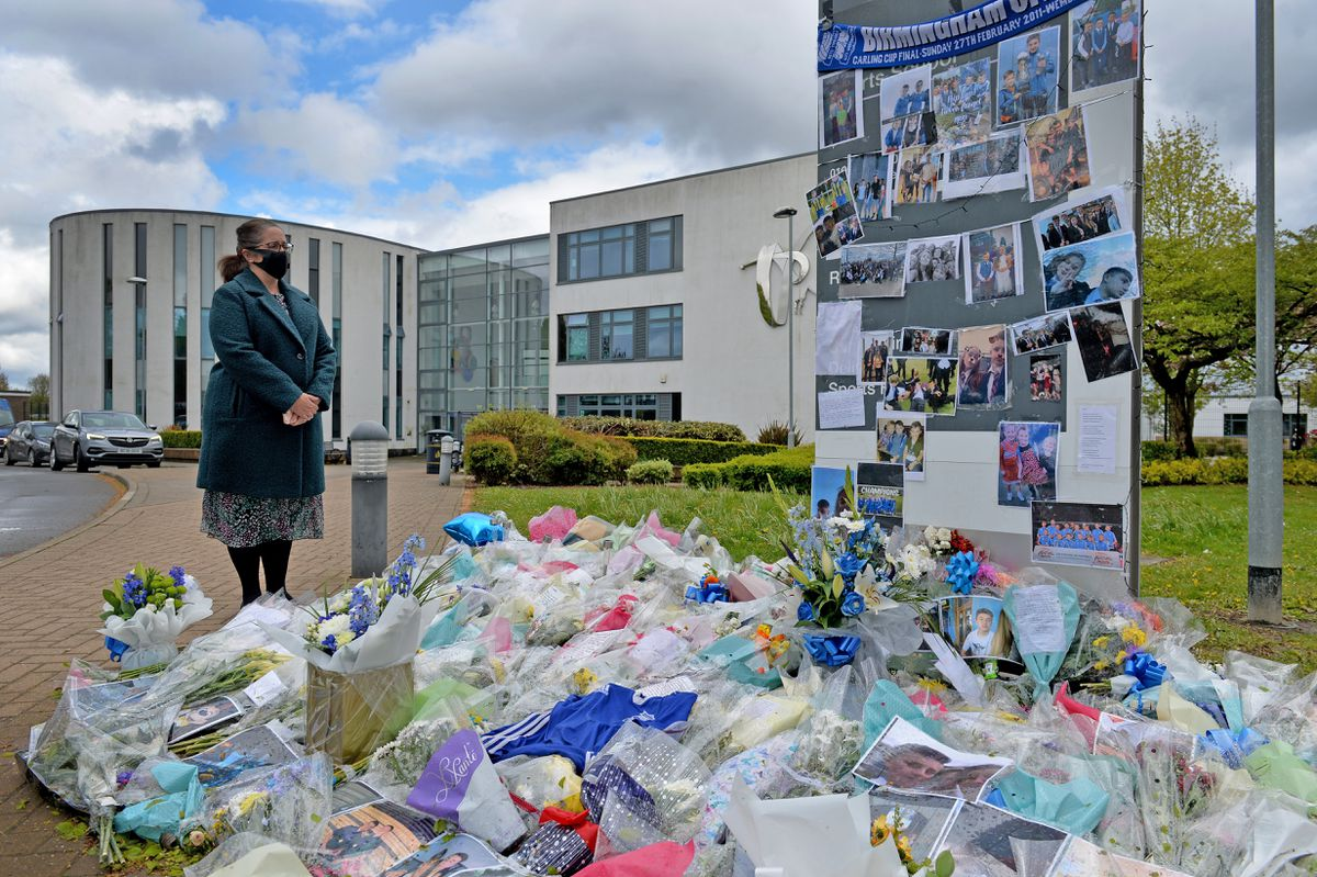 Headteacher, Claire Gilbert, with floral tributes left at the school