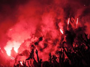 Football fans holding flares