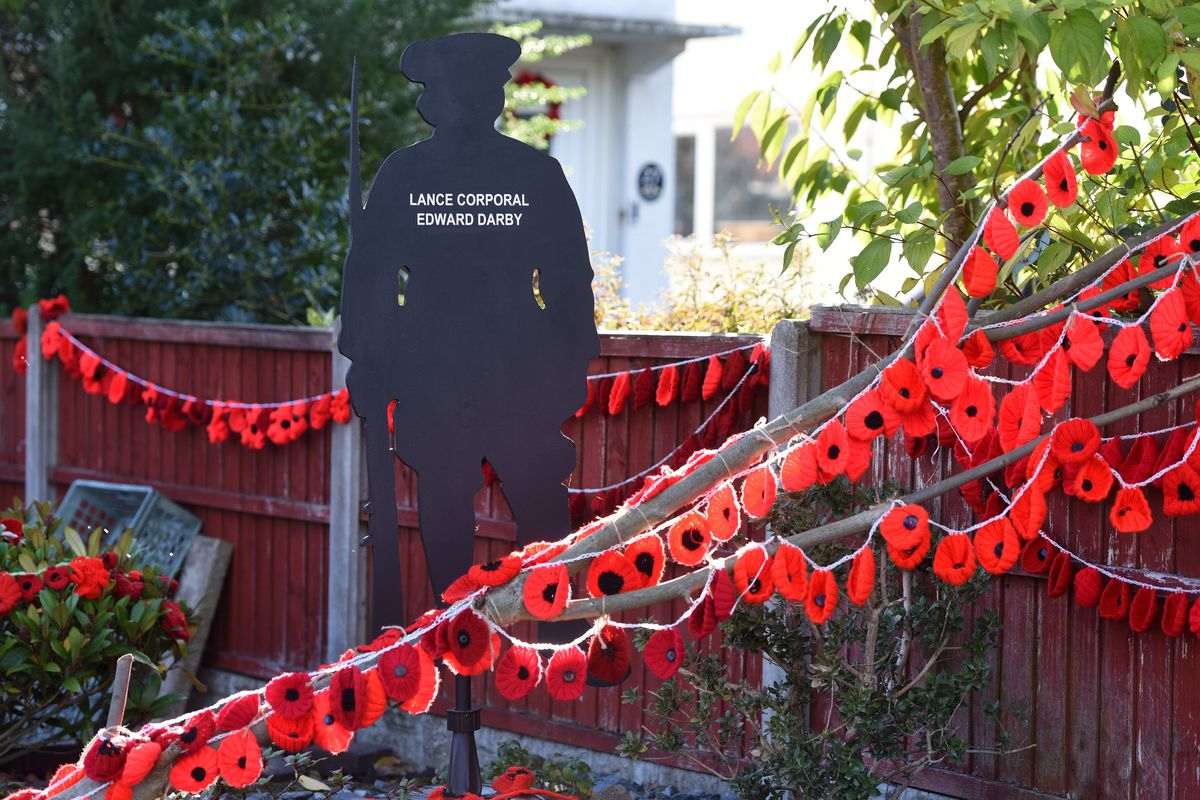 The silhouette of a soldier looks out on Poppy Road