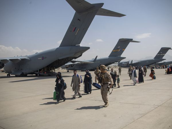 Members of the UK Armed Forces leading evacuees past ZZ171 (nearest camera), an Royal Air Force Boeing C-17A Globemaster III, at Kabul airport (LPhot Ben Shread/MoD/PA)