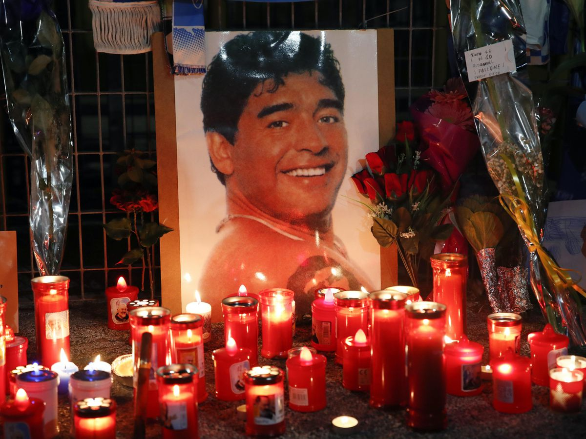 Candles and flowers left for Diego Maradona are seen outside the San Paolo in Naples
