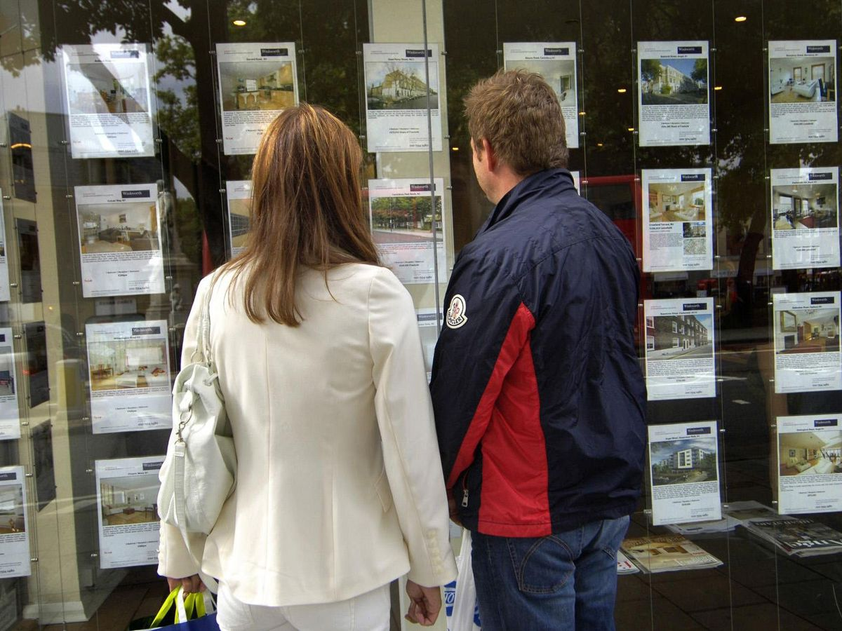 People looking in an estate agent's window