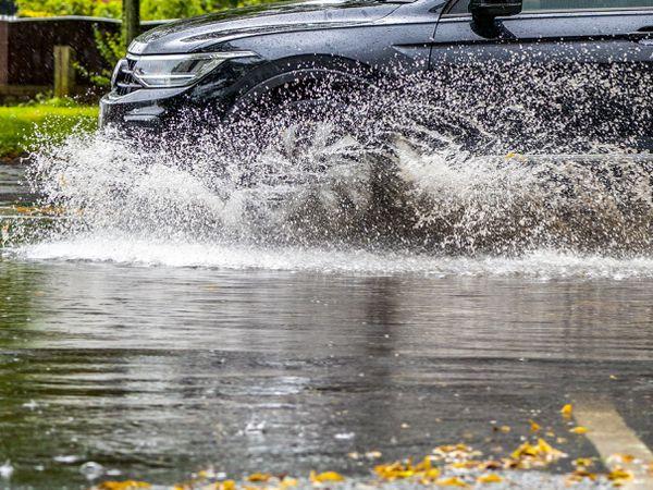 A car drives through standing water
