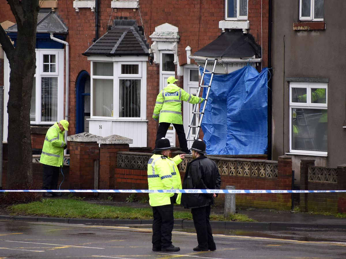Police staff cover broken windows of a property on Pensnett Road, Brierley Hill, West Midlands,