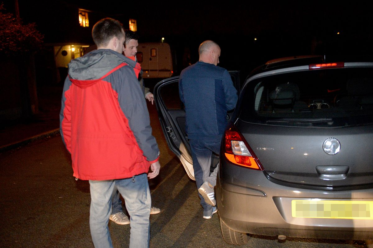 Suspect is escorted to an unmarked car during a series of dawn raids targeting drug dealers