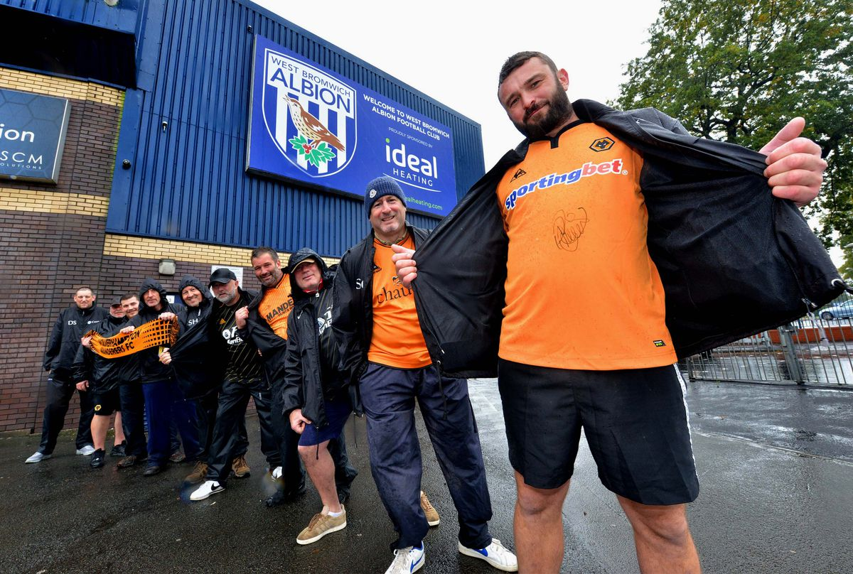 Pete Rogers and fellow Wolves supporters brave the rain at The Hawthorns as part of a fundraiser for his two-year-old daughter Clara