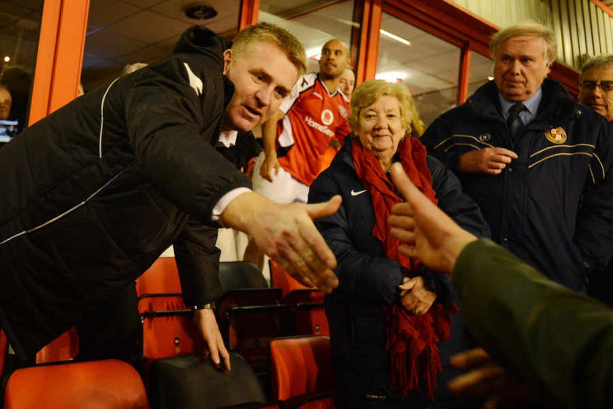 Dean Smith shakes hands with a supporter.