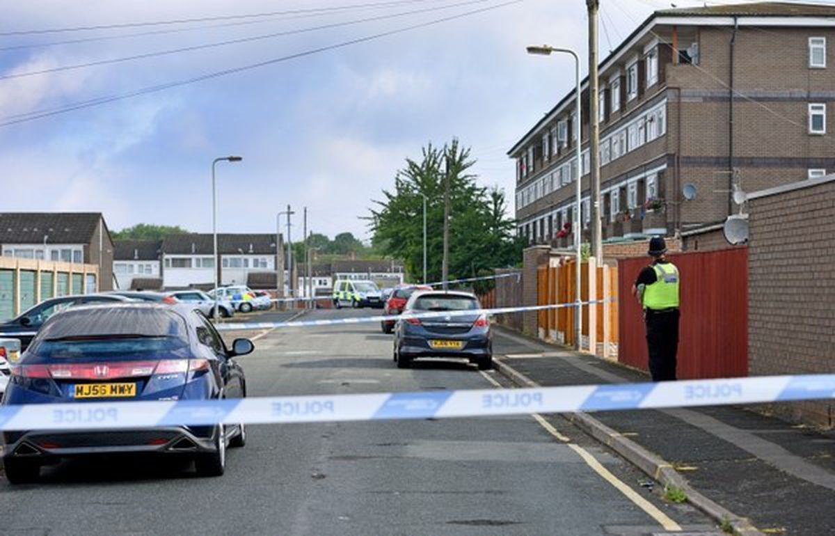 Police at the scene where Mr Haughton was shot in the head