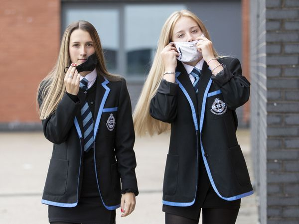 Students put on protective face masks