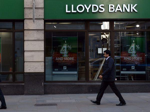 People walk past a Lloyds Bank branch