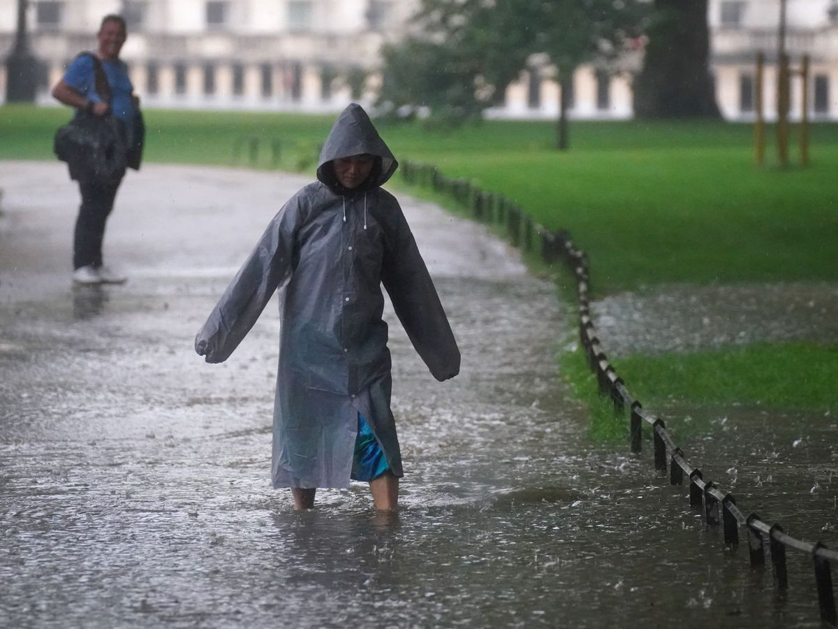 a woman walking through a large puddle