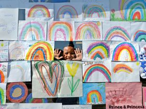 Children have designed rainbow pictures to go in the window of The Wall Heath Coffee Co, Kingswinford. Pictured peeping out from the rainbows is seven-year-old Theo Psaras