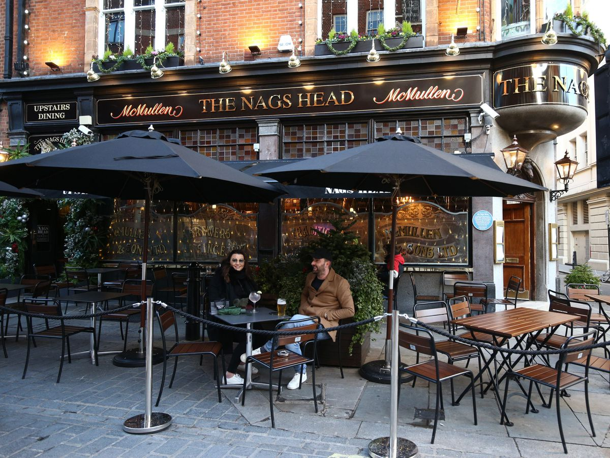 People drinking outdoors at The Nags Head pub in Covent Garden, London