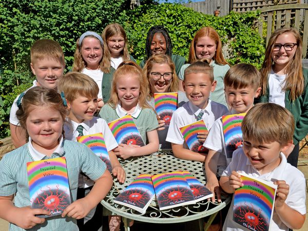 Ella Fletcher pictured with the children who contributed to the book, from Pool Hayes, Bentley West and Westfield primary schools