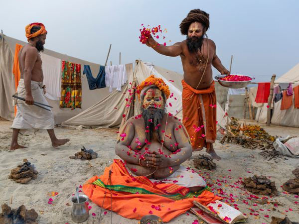 A Hindu Holy man prays as others shower flower petals on him