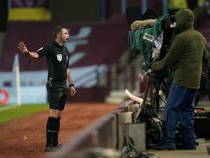 Referee Michael Oliver reviews a VAR decision and rules out a penalty