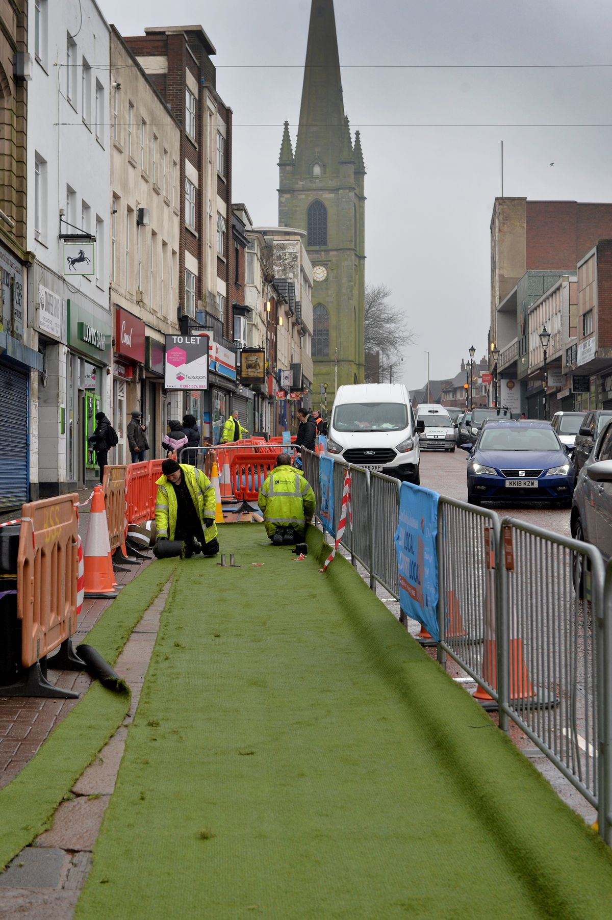Artificial grass is placed in parking lots on Dudley High Street to aid social distancing