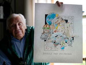 Artist Robert Seaman holds up the 365th daily doodle sketch in his room at an assisted living facility in Westmoreland, New Hampshire
