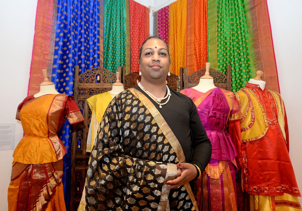 Curator Jaivant Patel next to some of the colourful outfits on display