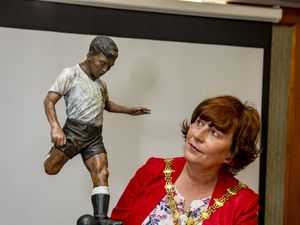 Mayor of Dudley Councillor Anne Millward looks at the Duncan Edwards Trophy and a poppy ball