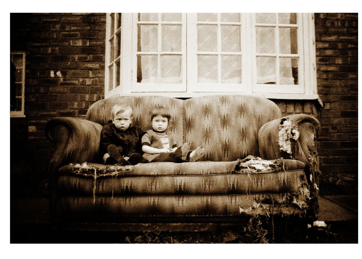 Two youngsters sitting on an old sofa outside their home