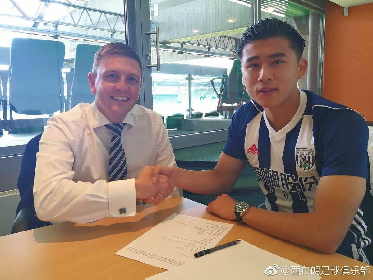 Zhang Yuning signs for Albion with former director Richard Garlick. One of the few times he wore the shirt.