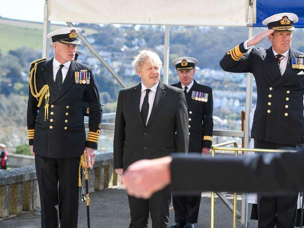 Boris Johnson stands between members of the military