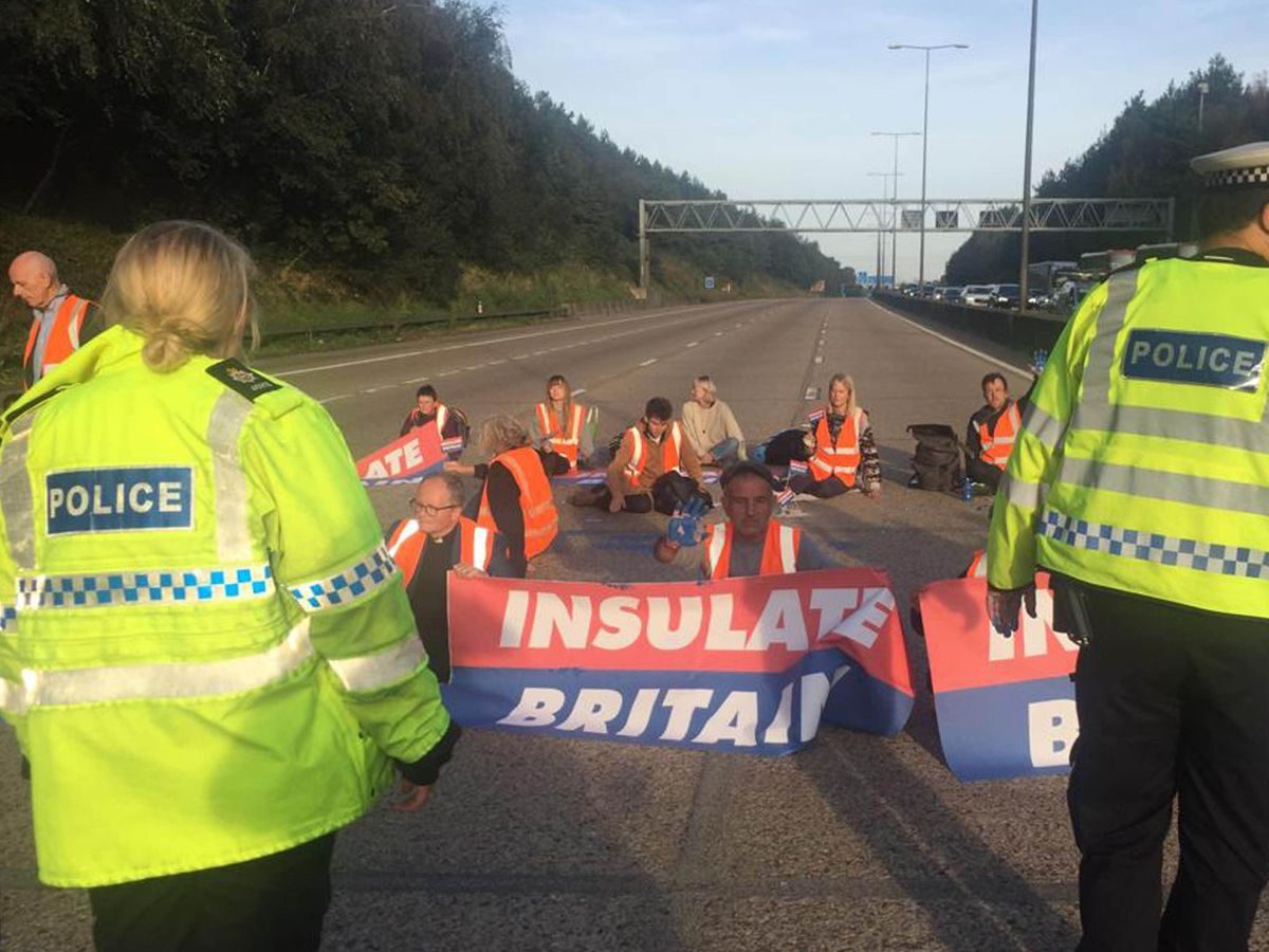 Handout photo issued by Insulate Britain of protesters occupying the clockwise and anti-clockwise lanes on the M25 in Surrey on Tuesday