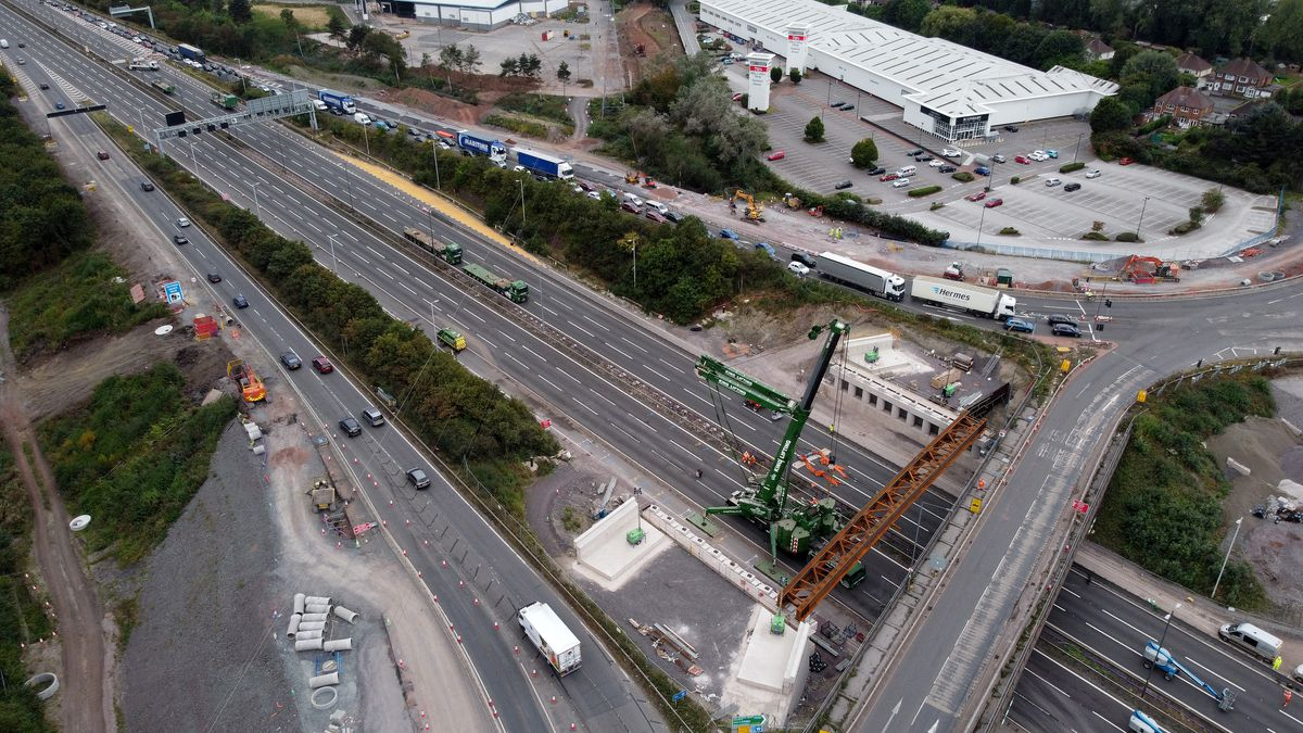 Bridge beams are being lowered into place by a large crane