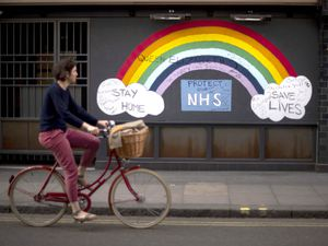 A woman cycling past a rainbow graffiti in support of the NHS in Soho, central London.
