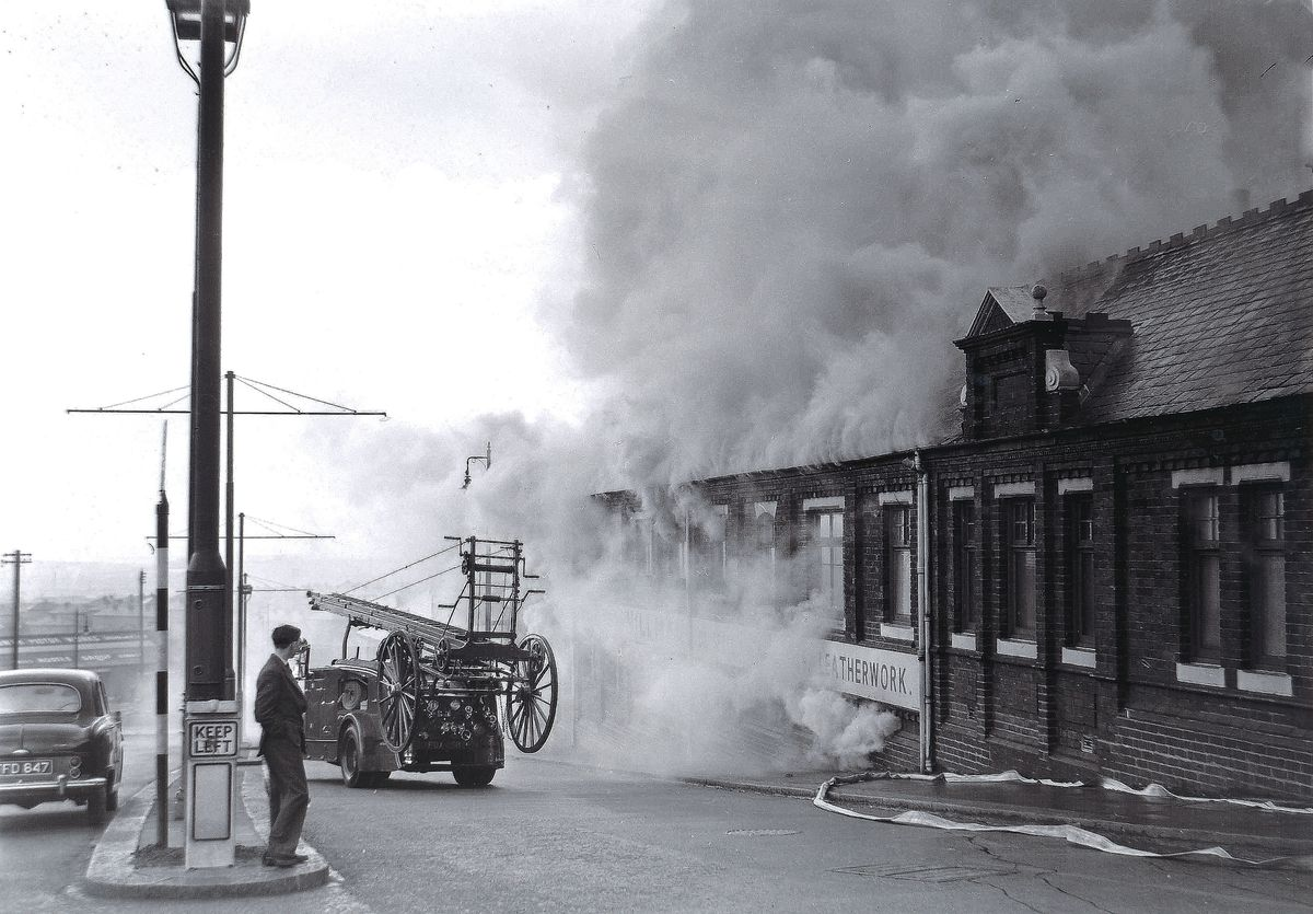 Smoke bellowing out of the machine shop as the fire engine arrives at Hillmans Leather Works, Dudley in April 1958.