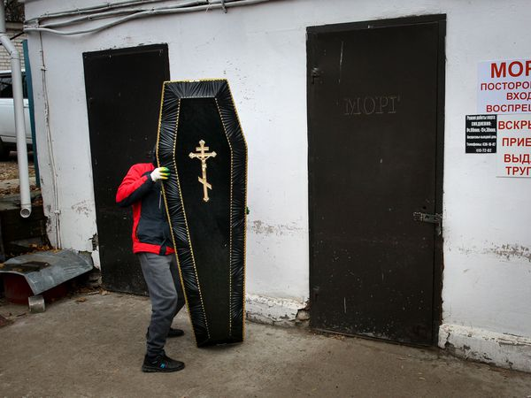 A funeral worker carries a coffin cover for a patient who died of Covid-19 at Infectious Hospital No 5 in Nizhny Novgorod, Russia