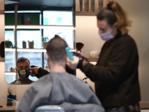 Hairdresser Dana Biezalo with a client at The Barbery in Southwark, south London