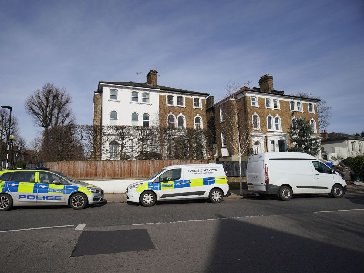 Police vehicles outside a property on Castlebar Road, Ealing, west London, where a woman in her 40s was found dead on Monday