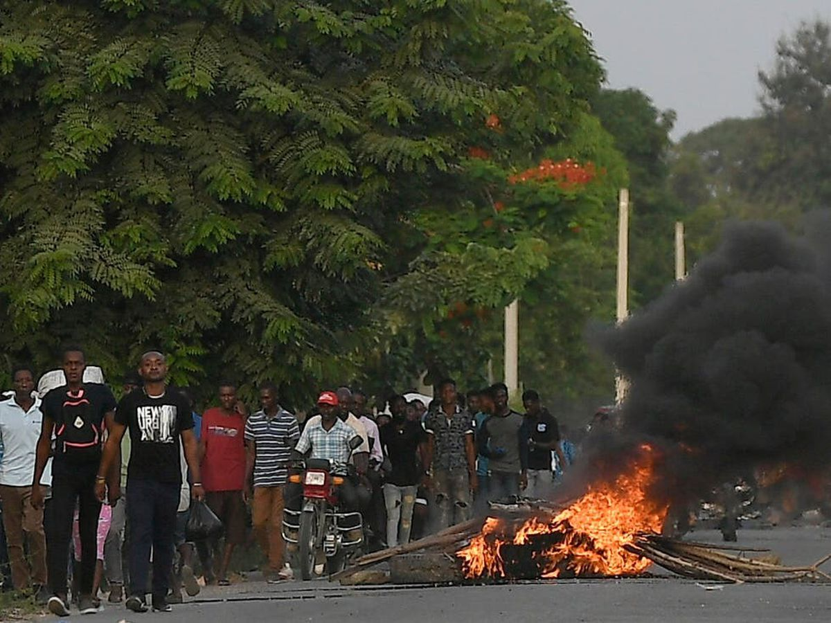 Men walk past a flaming barricade after violence broke out near the home town of late President Jovenel Moise