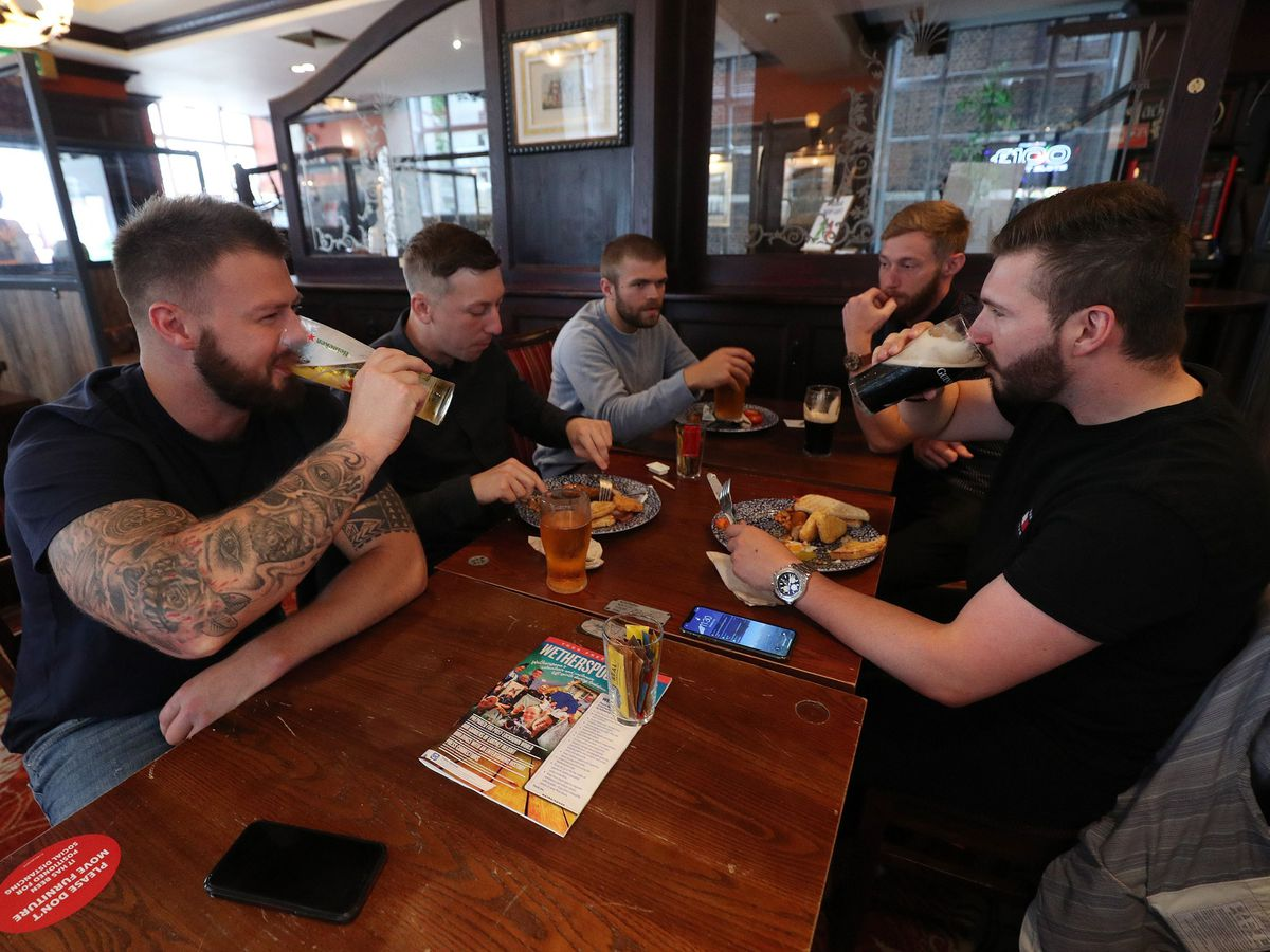 A group of pub customers enjoying food and drink